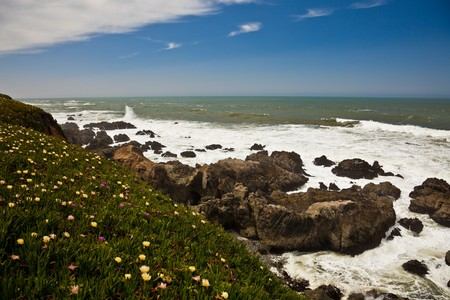 breading: Scenic view of waves breading on rocky ocean coastline under blue skies and clouds.  Stock Photo