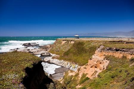 breading: Rocky ocean coastline. Scenic view of waves breading on rocky ocean coastline.