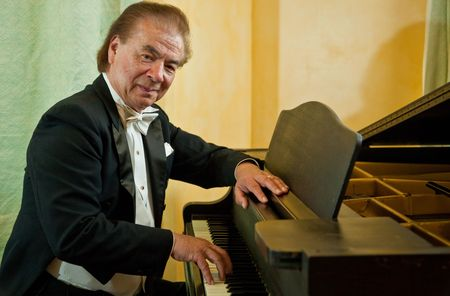 Senior man pianist spelen op een vleugel. Nikolai Massenkoff, de ster van het Massenkoff Russische Folk Festival. Stockfoto