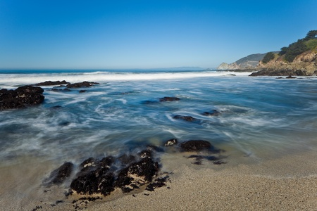 breading: Ocean coastline landscape.  Scenic view of waves breading on rocky ocean coastline under blue skies.  Stock Photo