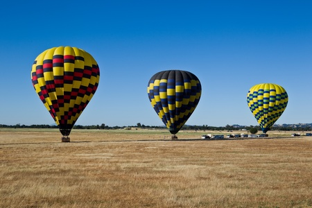 Hot air balloons are landing on a floor of Sacramento Valley in California. Stock Photo