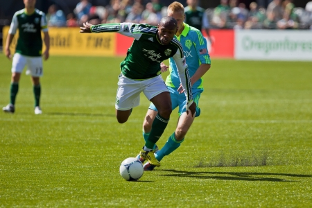 PORTLAND, OR - SEPT 15: Franck Songo'o #8 of the Portland Timbers battles for a ball with Andy Rose #25 of the Seattle Sounders during the game, on Sep 15, 2012 at Jeld-Wen Field in Portland, OR. Stock Photo - 15337132