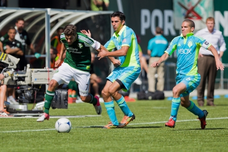 PORTLAND, OR - SEPT 15: The Portland Timbers Sal Zizzo #7 moves the ball against the Seattle Sounders Leonardo Gonzalez #12 and Osvaldo Alonso #6 during the game, on Sep 15, 2012 at Jeld-Wen Field in Portland, OR.