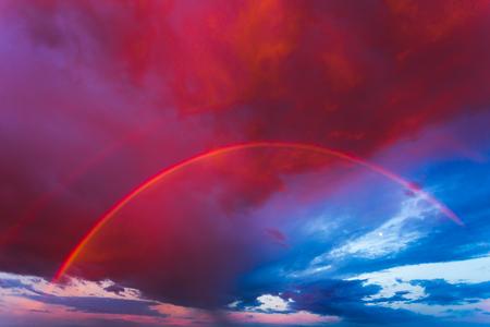 Double rainbow in the purple evening sky Stock Photo