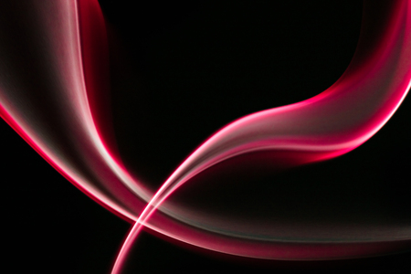 Sharp picture of red curved smoke forms in dark background