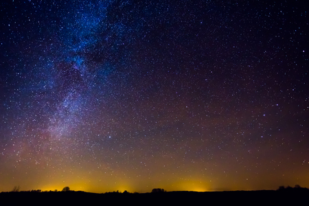 Night landscape image with colorful milky way and yellow light in the horizon Фото со стока