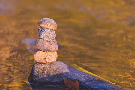 Stacked stone pyramid in front of yellow blurry background with bokeh