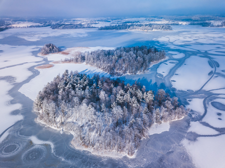 Aerial view of the winter snow covered forest and frozen lake from above captured with a drone in Lithuania.