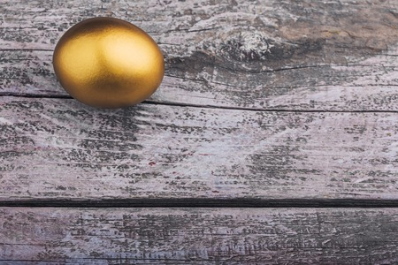 Background of Golden egg on a wooden surface Imagens