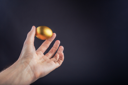 Man hand holding Golden egg on a black background