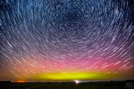 Star trails around the Polar Star or Polaris and green glowing display of Northern Lights or Aurora borealis in Lithuania