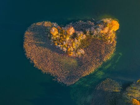 Aerial view over an island. The island is formed as a green heart. Surrounded by water, ocean, sea, lake. Autumn view