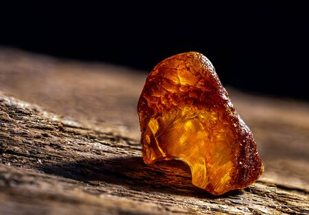 Natural amber. A piece of yellow transparent natural amber on large piece of dark stoned wood. Stock Photo
