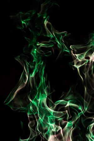 Green fire forms abstraction in black background