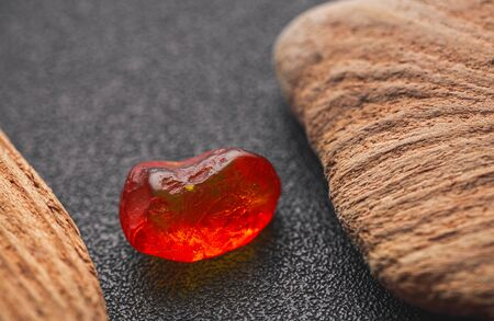 Natural amber. A piece of yellow transparent natural amber on a piece of textured wood