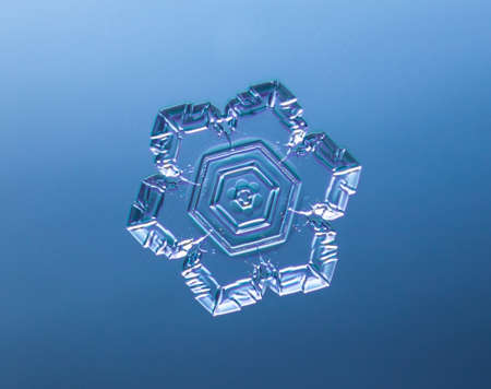 Snowflake on smooth gradient background. Macro photo of real snow crystal on glass surface. This is small snowflake with unusual pattern.