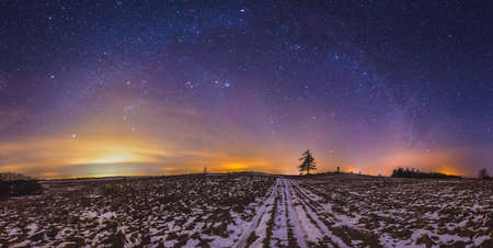 Milky way galaxy, night sky panorama with stars and snow on foreground