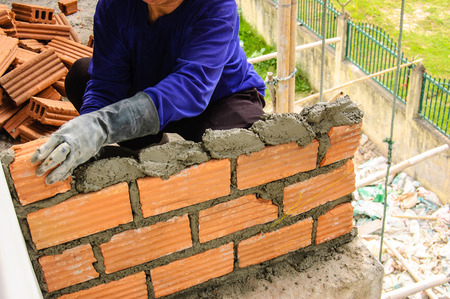 building wall: worker and brickwork Stock Photo