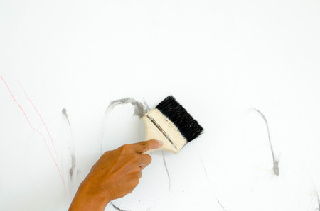 Hand holding and brushing to wall background Stock Photo