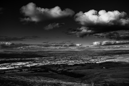 Scenic view from Pendle Hill, North- East, Clouds cast shadows over Lancashire Hills. In distance Yorkshire highest peaks:Pen-y-Ghent, Ingleborough, Whernside. Black and white. Forest Of Bowland. West Pennine Moors. Lancashire. England, UK
