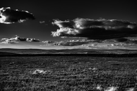 Scenic view from Pendle Hill, North, Clouds cast shadows over Lancashire Hills. In distance Lake District mountains. Black and white. Forest Of Bowland. West Pennine Moors. Lancashire. England, UK
