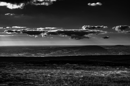 Scenic view from Pendle Hill,West. Clouds cast shadows over Lancashire Hills. In distance Blackpool and Irish sea. Black and white. Forest Of Bowland. West Pennine Moors. Lancashire. England, UK Stock Photo