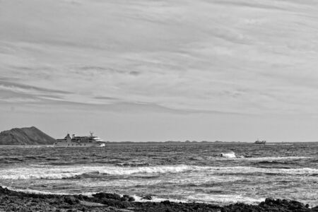 beautiful sea landscape with the ocean and a view of the Spanish island of De Lobos with a ship in the background Stock fotó