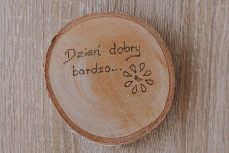 small original round mug coaster made of birch wood with a positive inscription in Polish