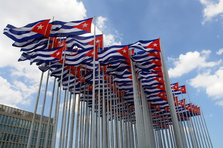 Cuban Flag On Flagpole Against Blue Sky With White Clouds 스톡 콘텐츠