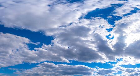 Panoramatic view of blue sky with clouds and sun in spring time