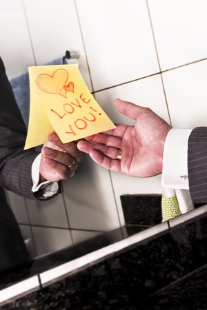 A man in a suit reads an I love you note taped to the mirror. photo