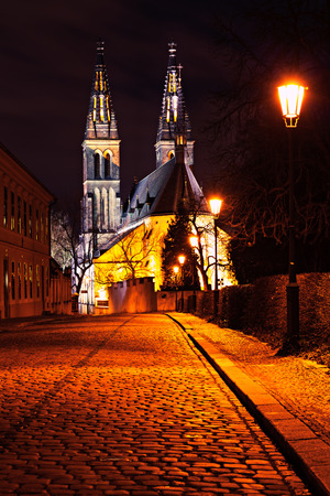 Street to Vysehrad church with shinning lamps in line at evening.