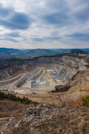 Surface mine in czech republic with forests and hills behind. Cloudy blue sky with sunbeams. Stock Photo