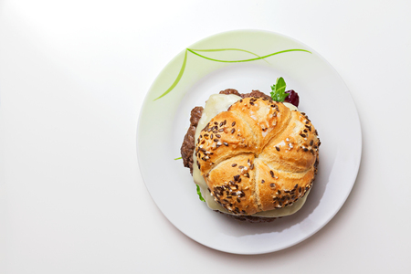 Rustic home made cheesburger with melting cheese and with dijonnaise sauce on white table on white background