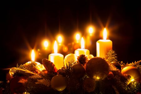 Christmas wreath with burning yellow candles, advent time, black background, copy space