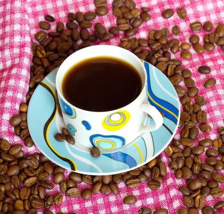 cup of cofee with cofee beans on pink bacground