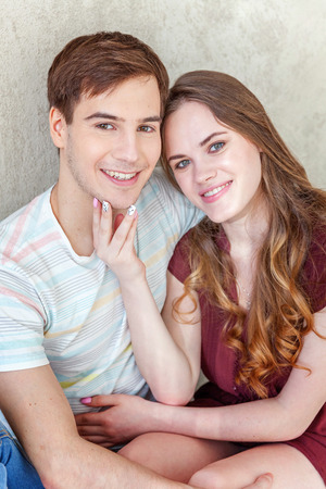 relying: Young couple in love. Couple supporting each other and relying on each other having nice time together. Young happy woman hugging her handsome boyfriend. Portrait of cheerful casual people in love, students having hopes, dreams, goals, bride and groom wit Stock Photo