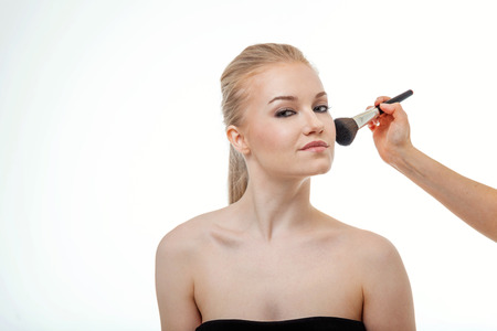 elegance fashion girls look sensuality young: Makeup artist applying powder for beautiful young woman on white background