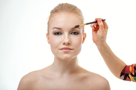 make up artist doing professional make up of young woman Stock Photo