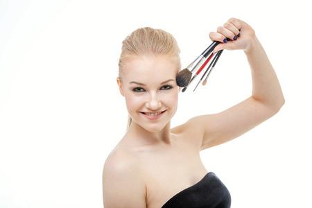 Closeup portrait of woman with makeup brush near face