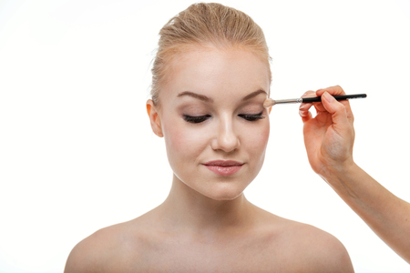 Makeup artist applying eye shadow for beautiful young woman on white background