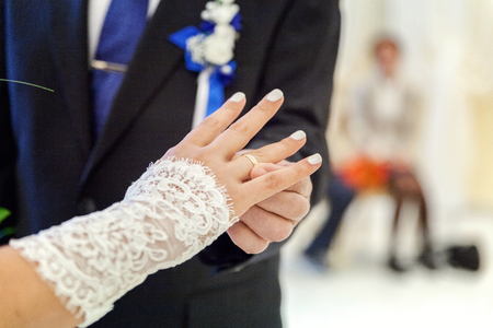 the groom wears a ring on the brides