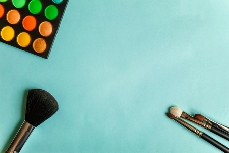 Colorful cosmetics on blue workplace. Top view and picturesque