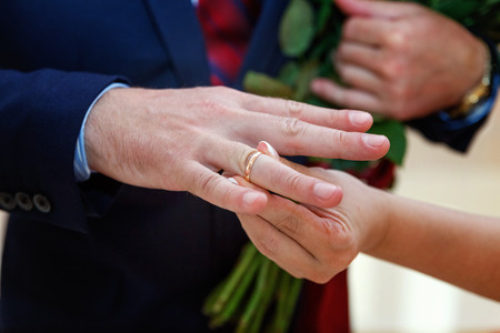 the bride wears a ring to the groom Standard-Bild