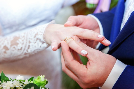 fingers put together: the groom wears a ring on the brides