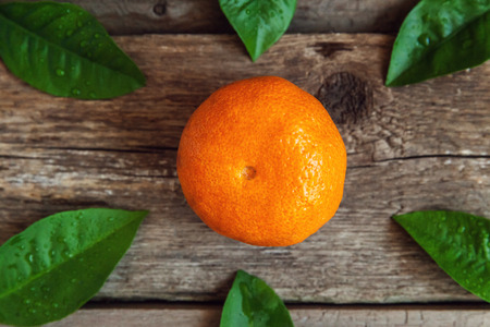 clementines: tangerine with leaves on wooden background
