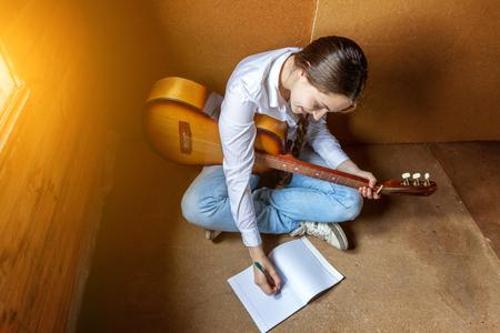 music lyrics: chica con una guitarra que escribe una canción
