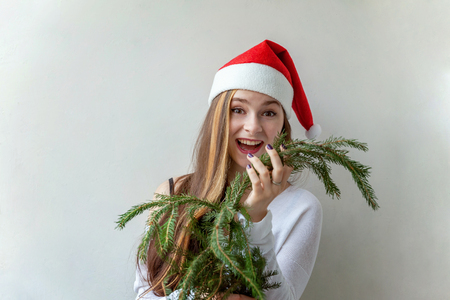 Girl in Santa hat with christmas green fir branches Stock Photo