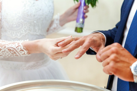 fingers put together: the bride wears a ring to the groom Stock Photo
