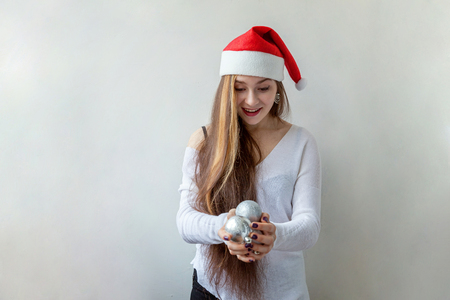 cutouts: Girl in Santa hat with christmas balls in the hands